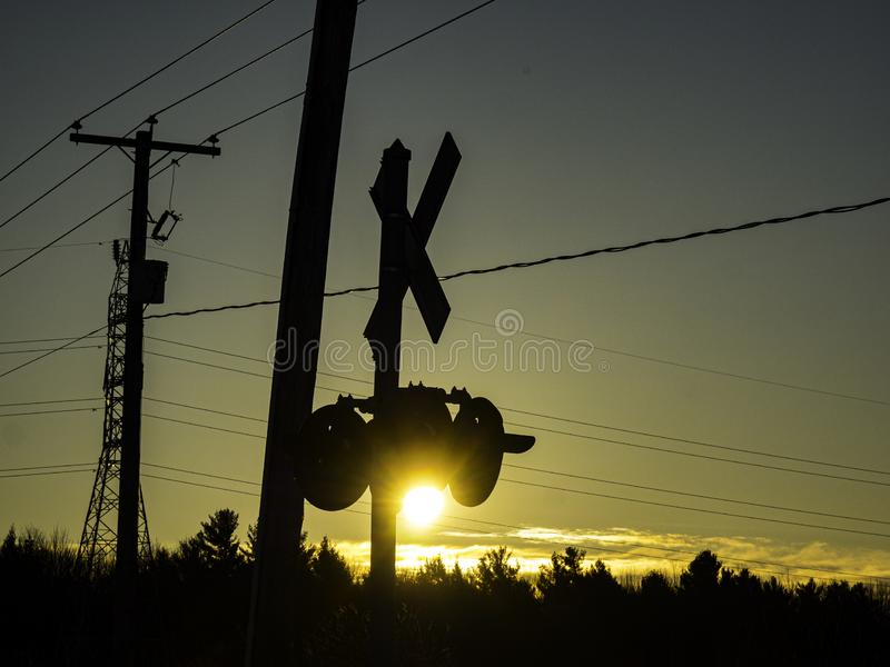 The sun rises near a railroad crossing. We can see an electric pylon and the shadow of the signal lights. In the distance there is the forest. Upton, Quebec stock images