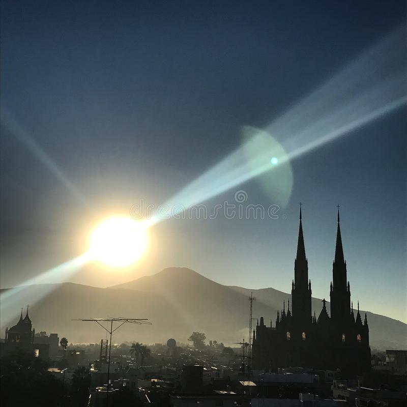 The sun rises over the city of Zamora, Mexico. The sun rises over the mountains, silhouetting the buildings of Zamora, Mexico, including the massive cathedral stock photo