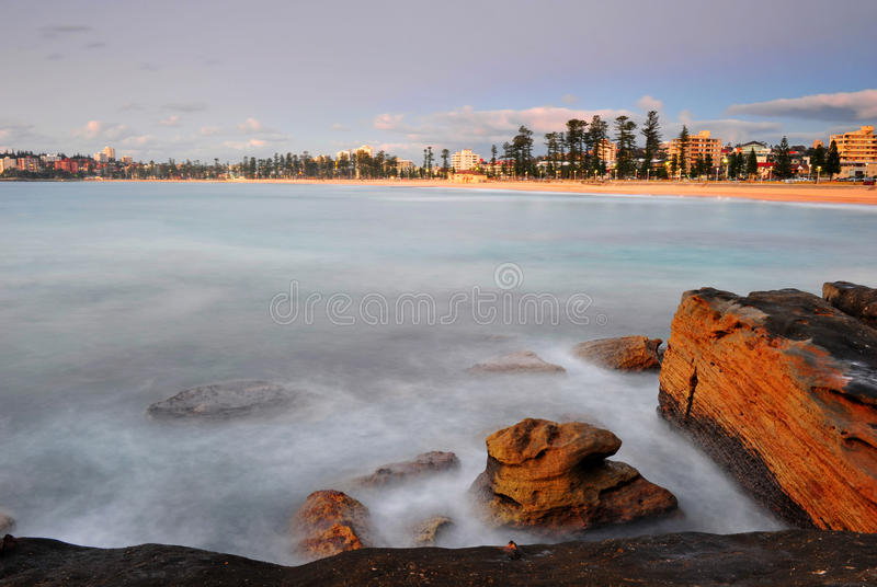 Sun rises over Manly Beach, Sydney, australia. Long exposure of waves swirling around rocks as sun rises over Manly Beach, Sydney, NSW, Australia royalty free stock photo