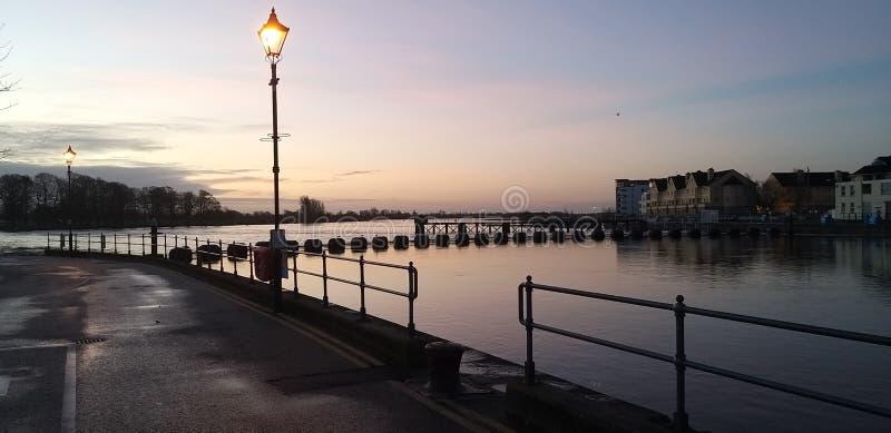 Sun rises over river stock image
