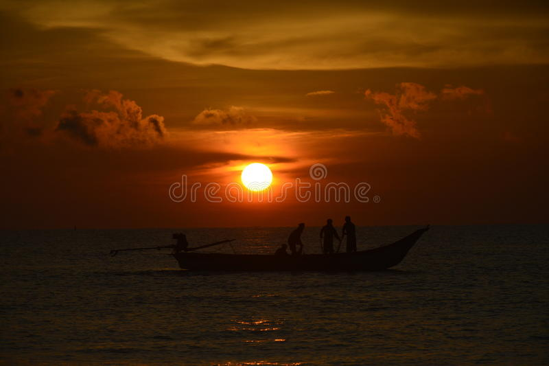 The sun rising above. Men fishing stock images