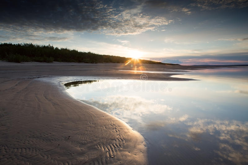 The sun rising above the river. stock image