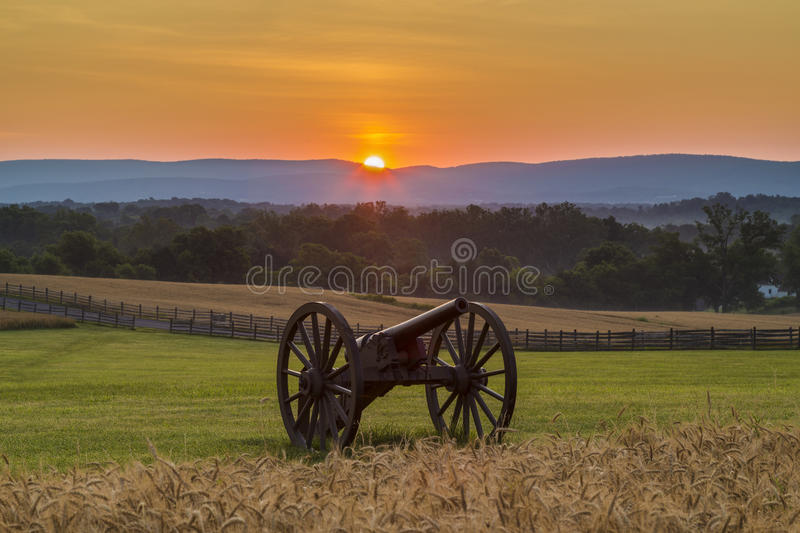 Sun rising behind artillery near a wheat field at Antietam. This is an image of the sun rising behind artillery at Antietam National Battlefield in Sharpsburg royalty free stock photo