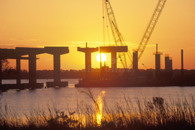 A sun rising behind a bridge building site. In New Bern, North Carolina stock photos
