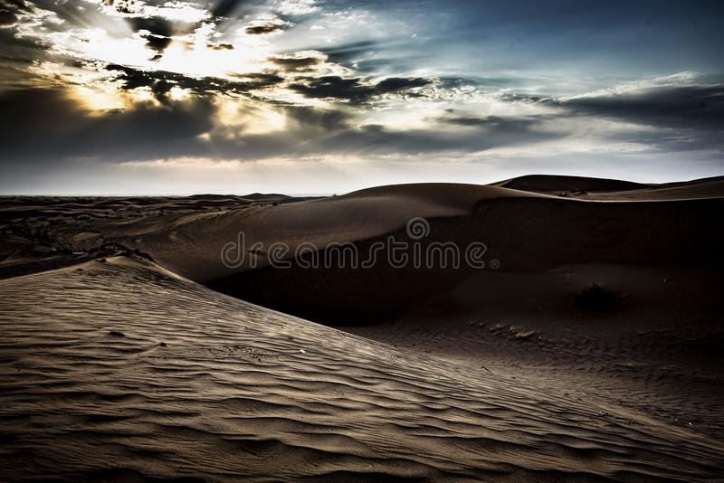 Dawn on the Maranjab Desert. The sun rising on the desert dunes drawing beautiful patterns on the sand, Kashan,Iran royalty free stock photo