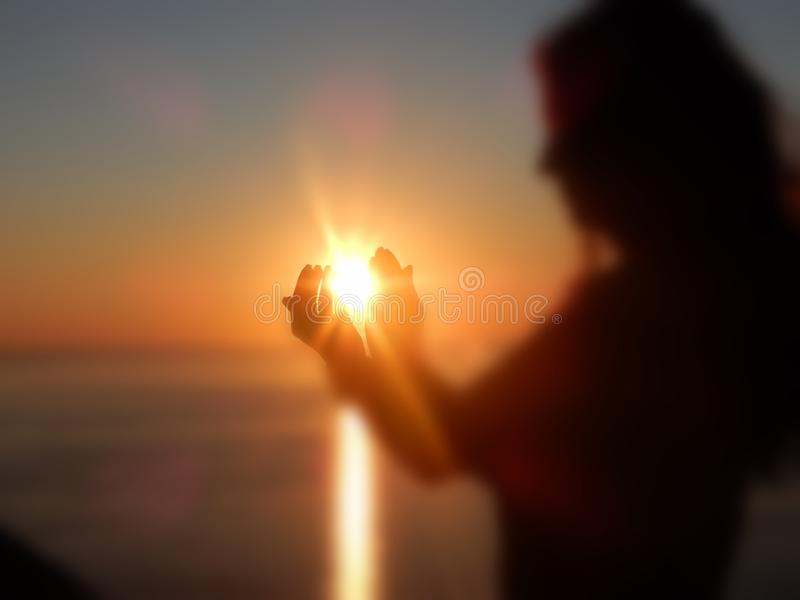 The Sun, rising from 2 hands stock photography