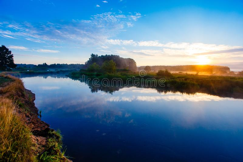 Sun rising over foggy countryside. Local river reflecting sky stock images