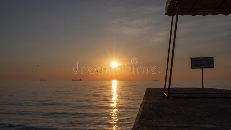 Sun rising over the calm sea and a stone pier with a sign on it stock photography
