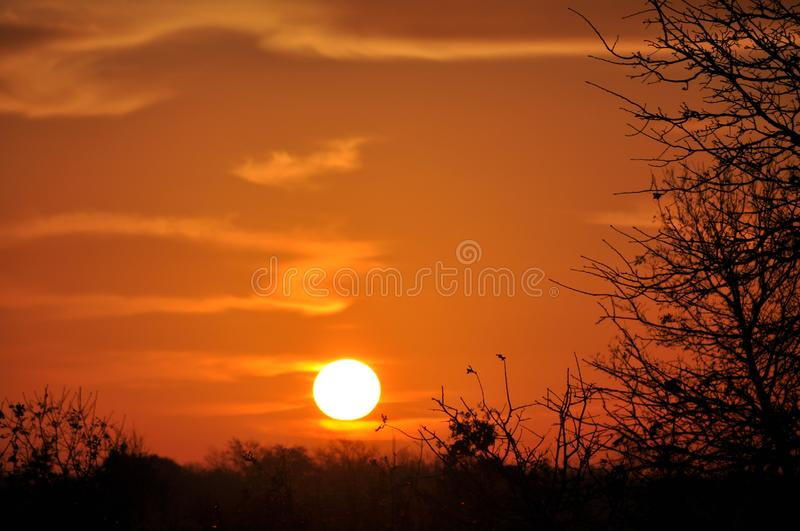Sun rising over rural landscape, with sky and clouds glowing. In deep orange shades royalty free stock photos