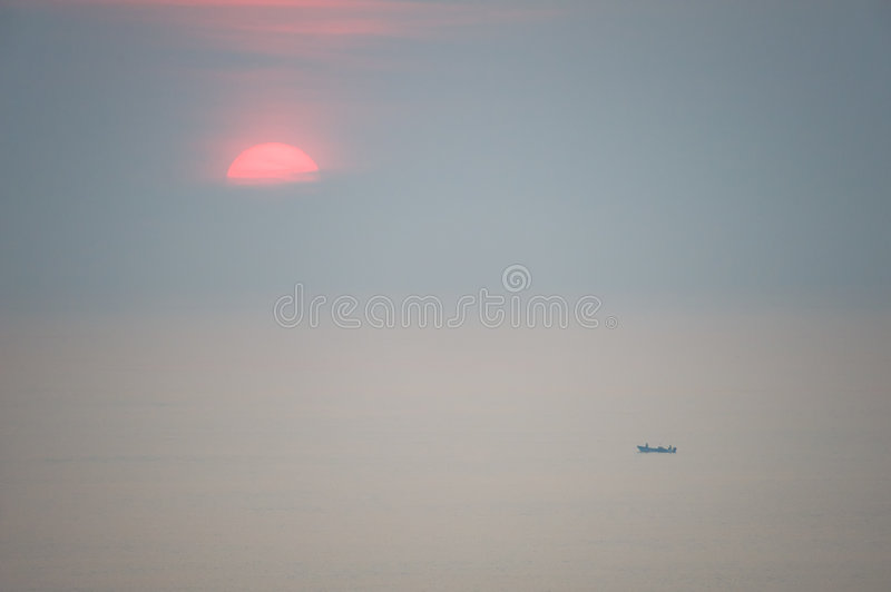Sun rising over vast ocean. Scenic view of sun rising over vast ocean with small fishing boat silhouetted in foreground stock photos