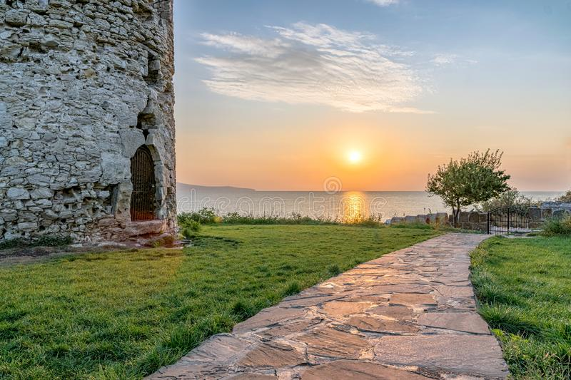 Sun rising from the sea on the Black Sea Coast. Alley at sunrise in Nessebar ancient city with ancient Tower at the left. Nesebar. Nesebr is a UNESCO World royalty free stock photography