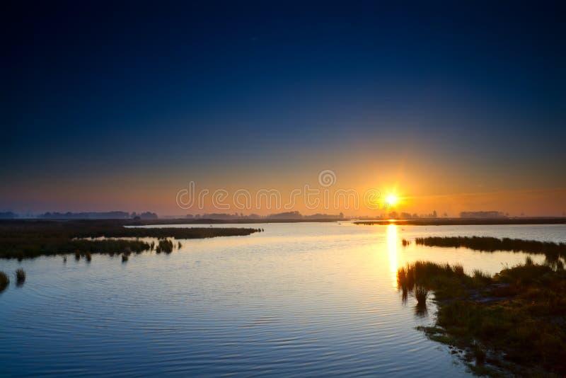 Sun rising up over blue lake stock image