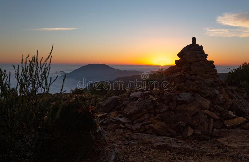 Sun rising up over a horzon of fog in Blue Mountains. A sea of fog all the way to the horizon line views from the mountain top at Lockleys Pylon in Blue stock photography
