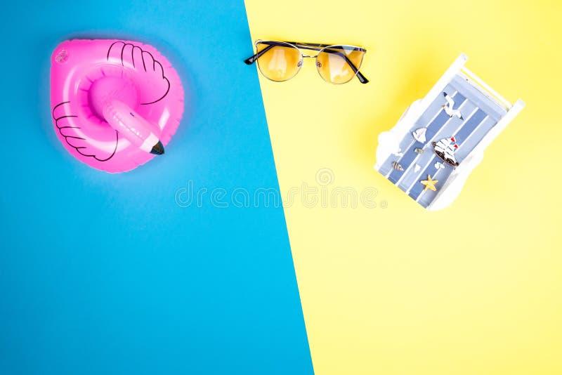 Sun-Ruhesessel, aufblasbarer Flamingo und Sonnenbrille lokalisiert auf buntem Hintergrund Tropischer Ferienhintergrund Sun-Ruhese lizenzfreie stockfotografie