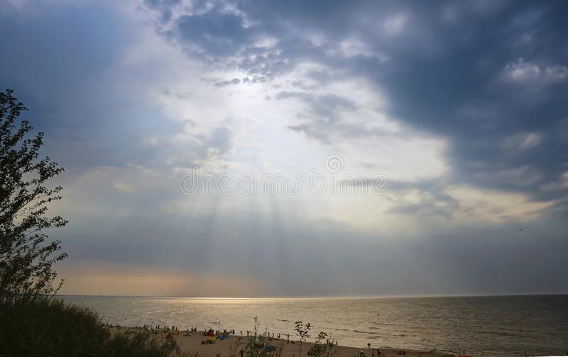 Storm clouds at sea, the sun`s rays breaking through the clouds royalty free stock images