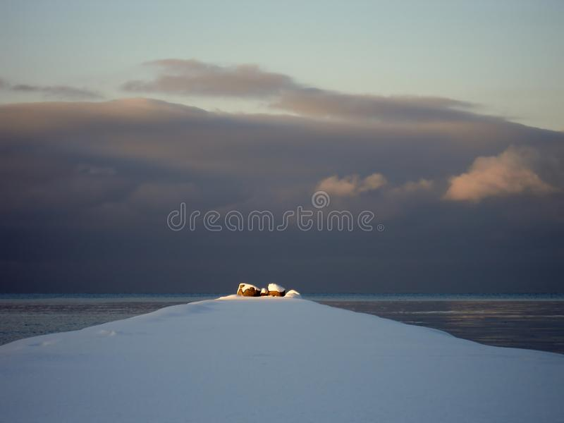The sun`s rays illuminate the  end of the marine breakwaters royalty free stock photos