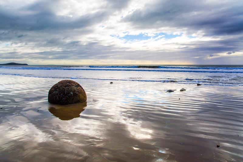 The sun's rays are reflected in the ocean. Moeraki's huge round boulders on a sandy beach. The Pacific ocean tide begins. New Zealand. The sun's rays are royalty free stock photo