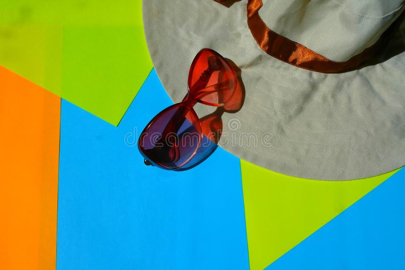 Sun-Schutzbrillen, Hut auf blauem und gelbem Hintergrund lizenzfreies stockbild
