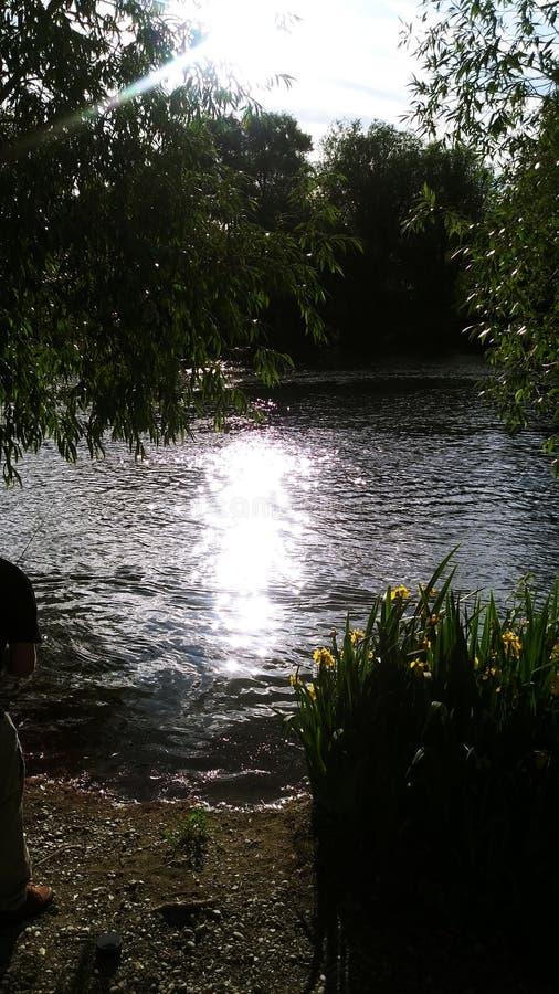 Sun se couchant par la rivière images libres de droits