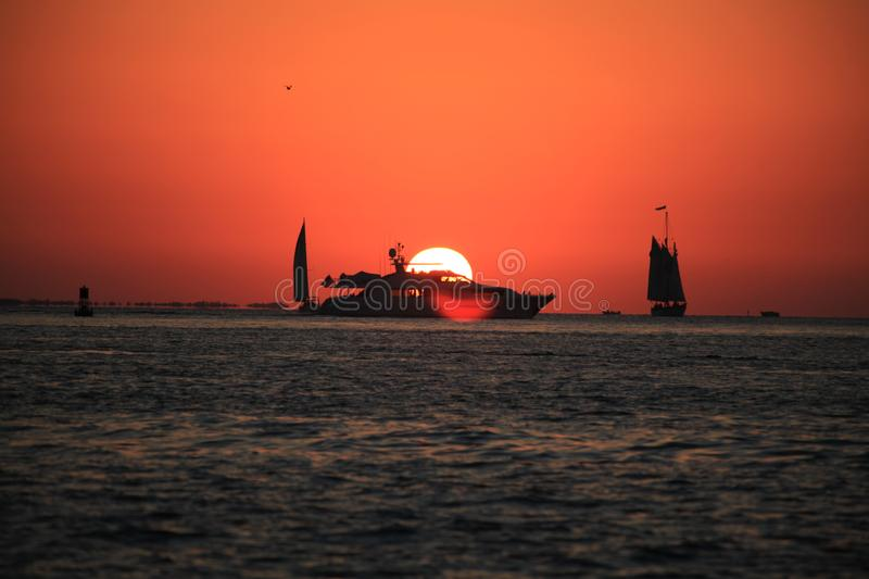 Sun set, boat and sailing. On the ocean stock image