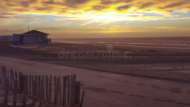 Sun Set in Noordwijk the Netherlands. Sky, beach, travel, fence, sand, waves, ocean, sea, yellow, life, guatd, hurt, hut, empty, dusk, clouds, view, coast royalty free stock image