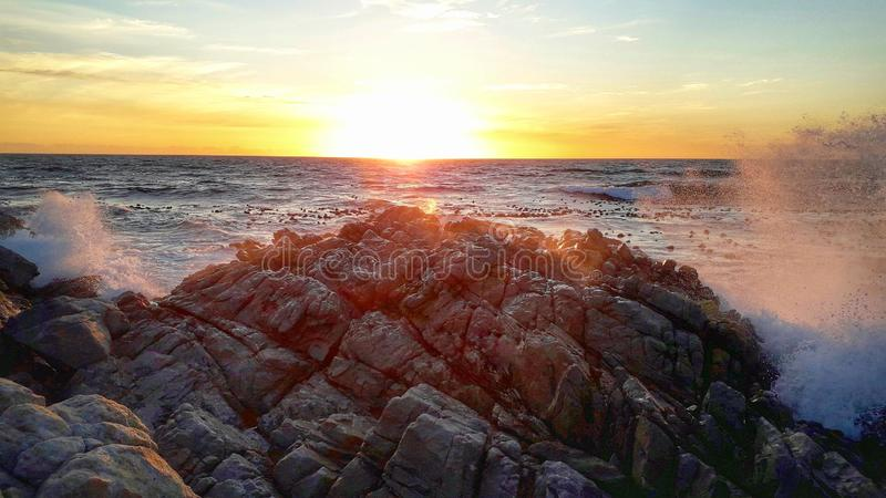 Sun set, Ocean, Rocks, Splash, Sky image stock