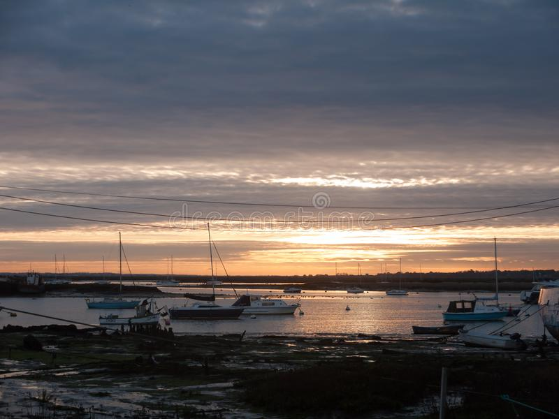 Sun set sky dramatic clouds sea front beach harbor marina boats. Moored landscape; west mersea, essex, england, uk stock photo