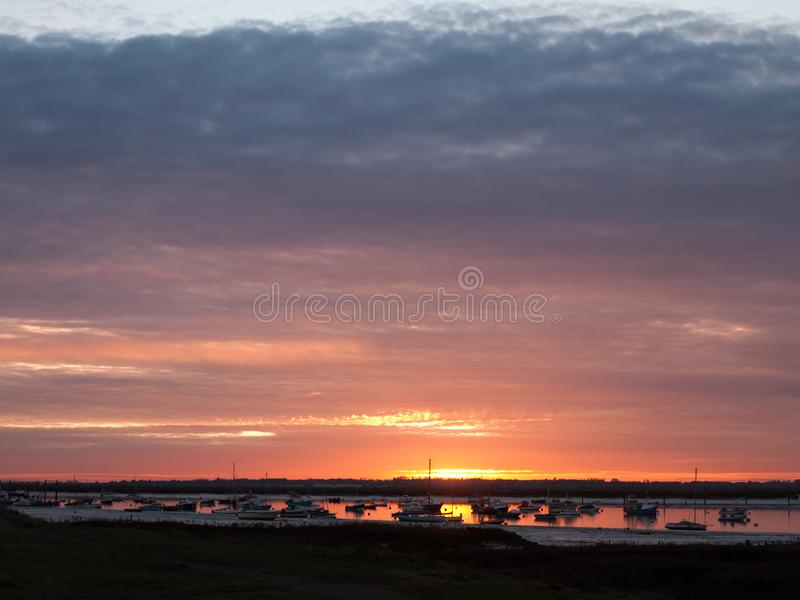 Sun set sky dramatic clouds sea front beach harbor marina boats. Moored landscape; west mersea, essex, england, uk royalty free stock image