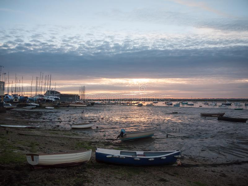 Sun set sky dramatic clouds sea front beach harbor marina boats. Moored landscape; west mersea, essex, england, uk royalty free stock photos