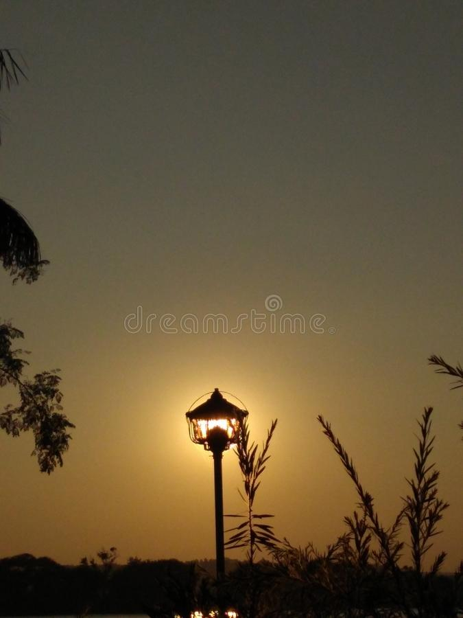 Sun set in a sky look a lamp in background royalty free stock images