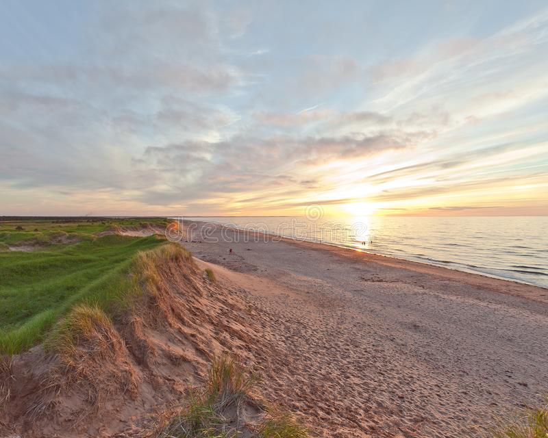 Sanddunes of Prince Edward Island. The sun sets on a beach on Prince Edward Island with beautiful sand dunes visible. The waves crashing against the PEI beach royalty free stock photos