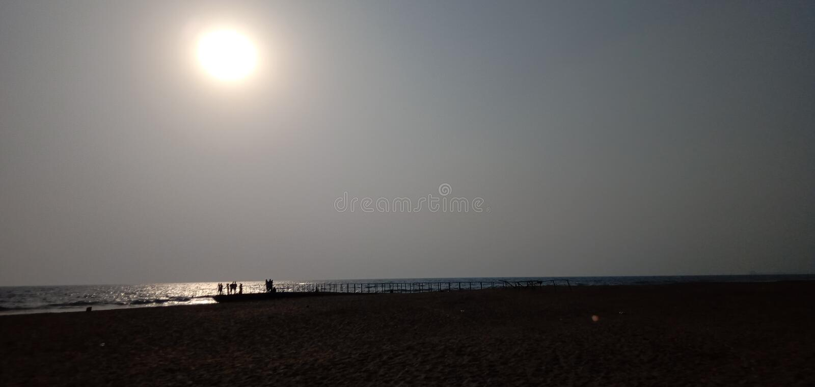 The sun sets on the beach by the sea. Many people water royalty free stock photo