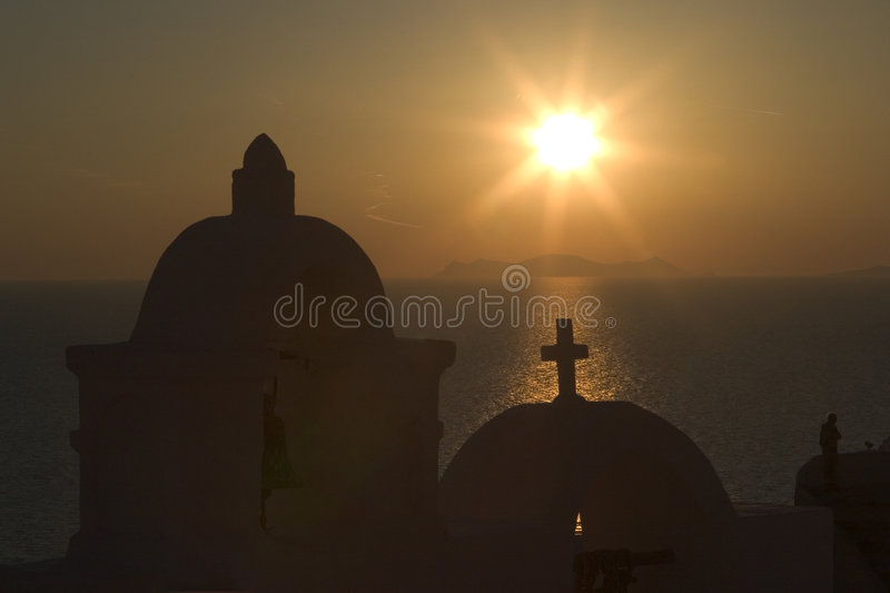 The Sun Sets Behind One Of The Many Orthodox Churches In The Town Of Fira, Santorini Stock Photos