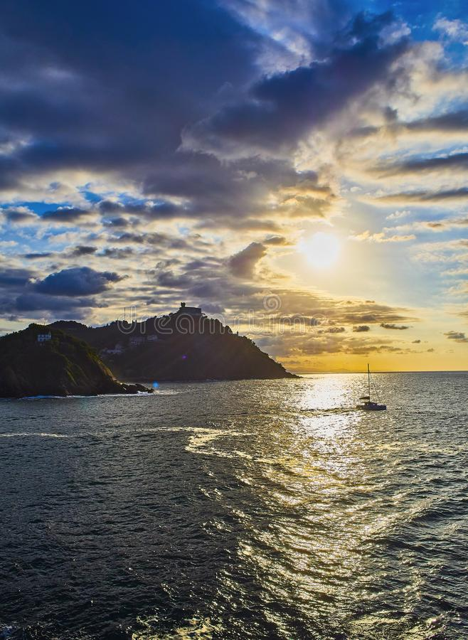 The sun sets behind the Santa Clara Island and The Igueldo Mount. The Concha Bay, San Sebastian. Spain. stock images