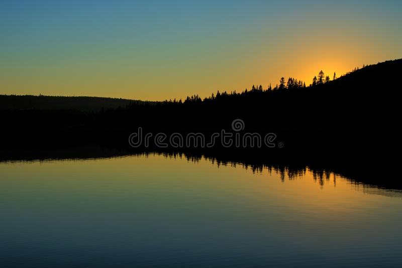 Sunset On Big Nictau Lake. The sun sets behind the trees at the edge of Big Nictau Lake within Mount Carleton Provincial Park in the province of New Brunswick royalty free stock image