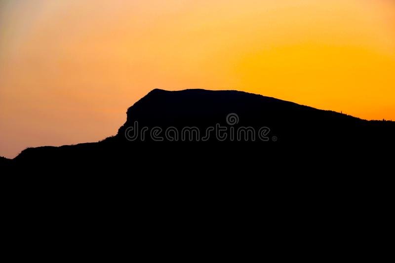 The sun sets and the evening is coming. The day is over, and the west behind the mountain is tomorrow stock image
