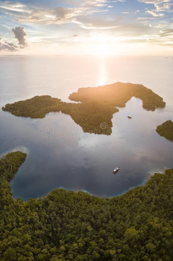 Aerial View of Sunset and Islands in Raja Ampat. The sun sets over a beautiful set of islands in Raja Ampat, Indonesia. This tropical region is known as the ` royalty free stock image