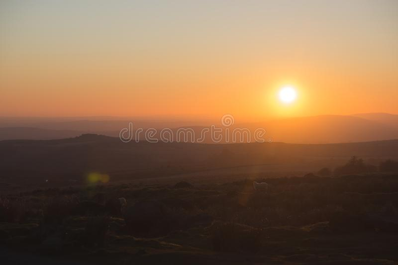The sun sets over Dartmoor, UK. A view of the moors at sunset over Dartmoor, UK stock photos