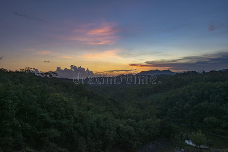 The sun sets over the hills royalty free stock image