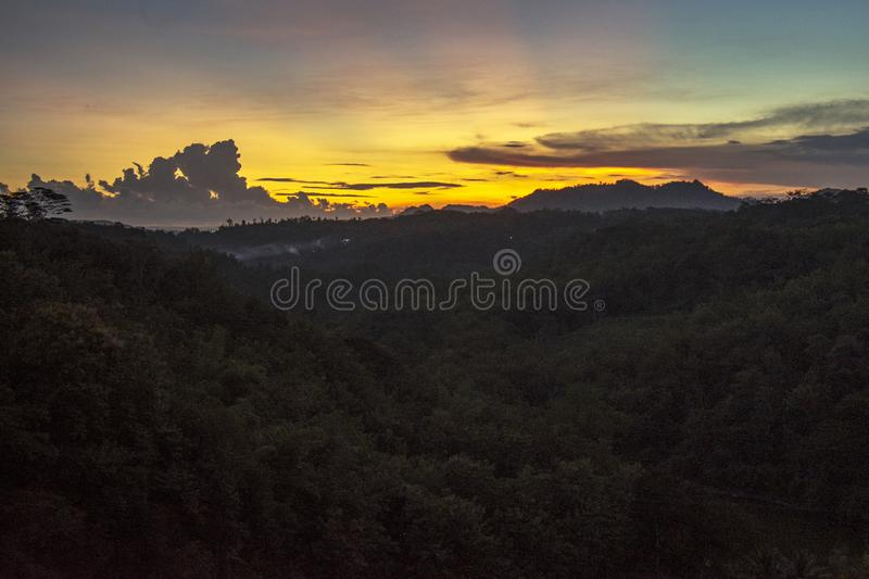 The sun sets over the hills royalty free stock photo