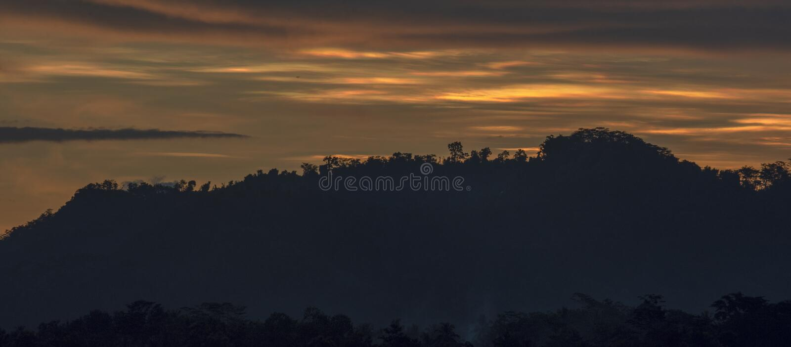The sun sets over the hills stock image