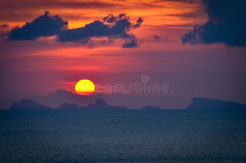 Sun sets over hilly horizon in depp red colors stock photos