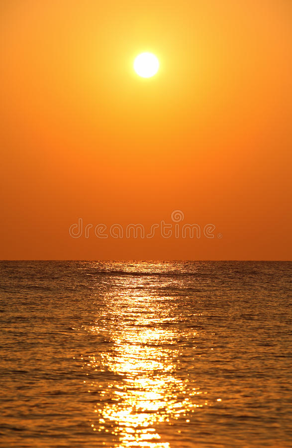 Sun sets over horizon. Sea, orange sun's reflection in sea water royalty free stock images