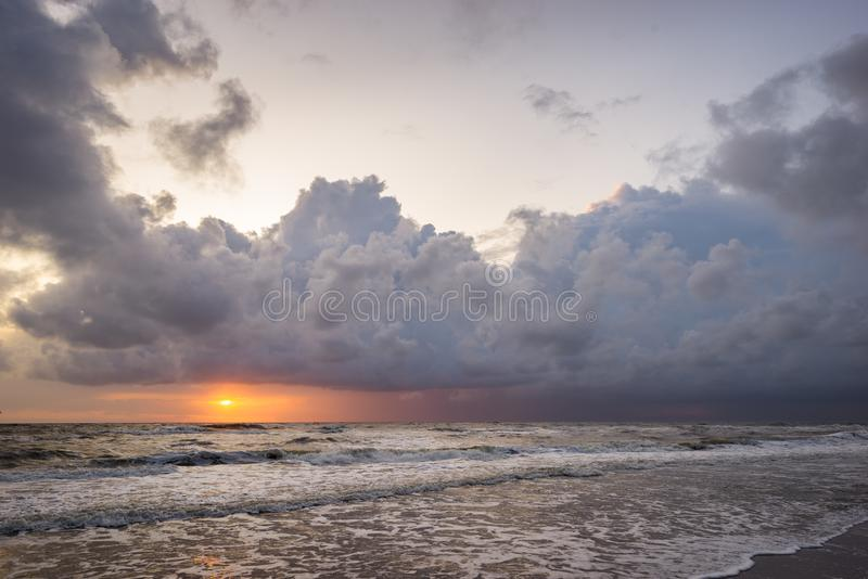 Sun sets over the sea below dramatic storm clouds royalty free stock images
