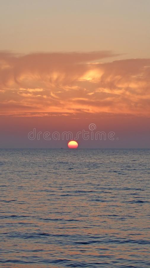 Sun setting in evening sea stock photo
