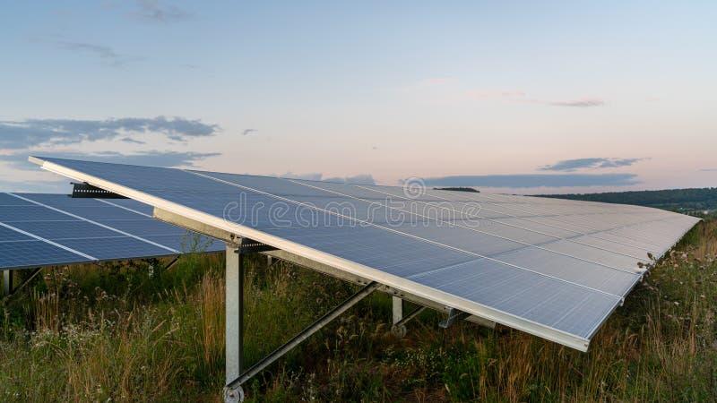 Sun sets on solar energy farm. Sun sets on solar energy panels on farm stock photos