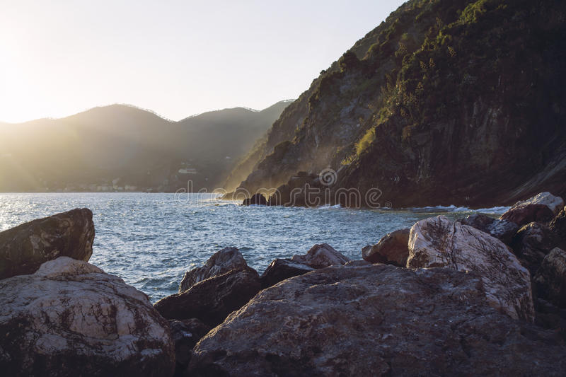 Sun setting against the Ligurian mountains by the ocean, creating golden vapors of waves hitting the rocks. Heavy boulders in foreground, hazy mountains in stock photo