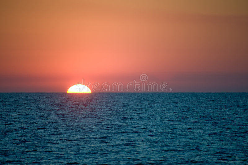 Sun setting behind sea horizon royalty free stock photos