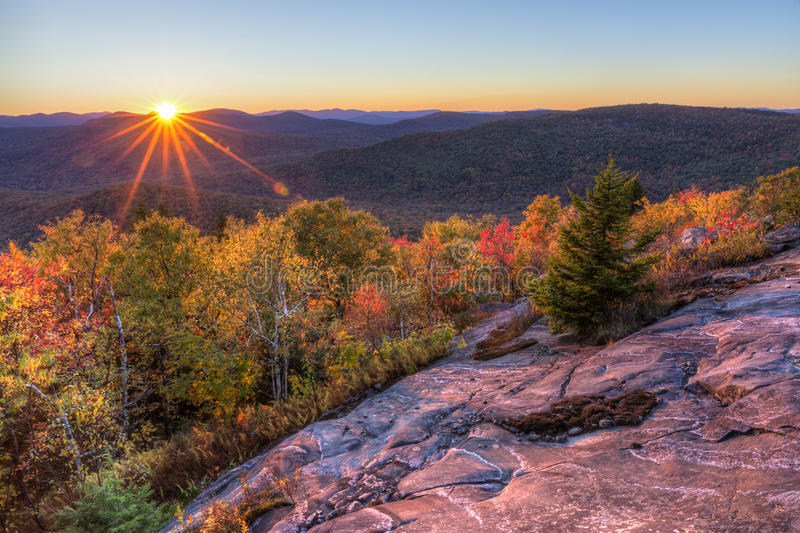 Sun Setting Behind Seneca Mountain. Colorful Autumn Sunset over Seneca Mountain from an overlook on Hadley Mountain in the Adirondack Mountains of New York stock photo