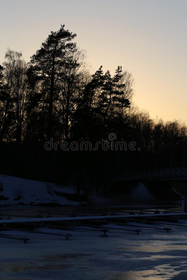 Sun Setting Behind a Forest and Frozen Sea in Espoo, Finland. Sun setting behind a small forest in Espoo, Finland. In the foreground of this photo you can see royalty free stock image